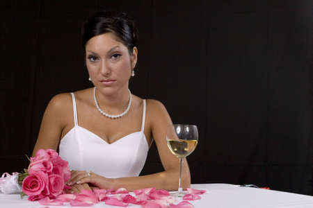 Bridal portrait over black background with pedals and champaign glass photo