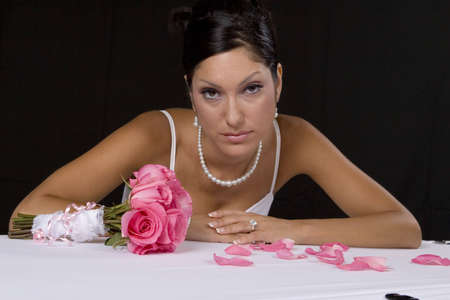 Bridal portrait over black background with pedals photo