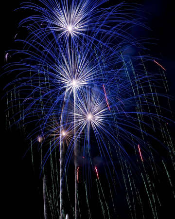 Multiple blue firework explosions during celebration