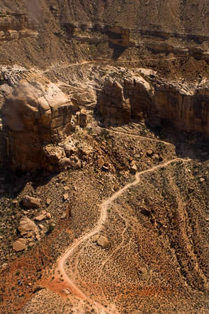Switchback trail on the canyon wall in the Grand Canyon that leads to Havasua Falls with horse trains on the trail, as seen from helicopter.