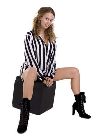 Young woman in referee black and white striped shirt over white background
