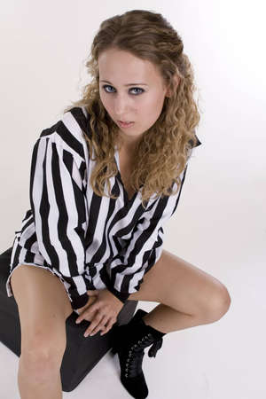 Young woman in referee black and white striped shirt over white background Imagens - 14261341