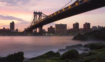 Manhattan Bridge from Brooklyn near sunset with mossy rocks photo