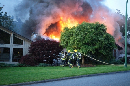 house on fire: Firefighter fighting with fire burning house
