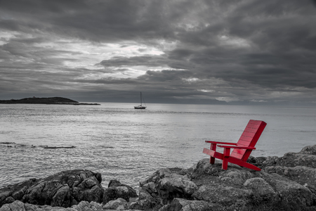 Red chair on ocean side rocks contrasts with the stormy black and white background.