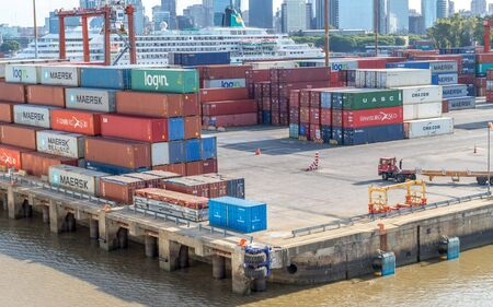 Buenos Aries / Argentina - January 19, 2020. Cargo containers moved by cranes are stacked around Puerto Madero awaiting shipping to other countries .