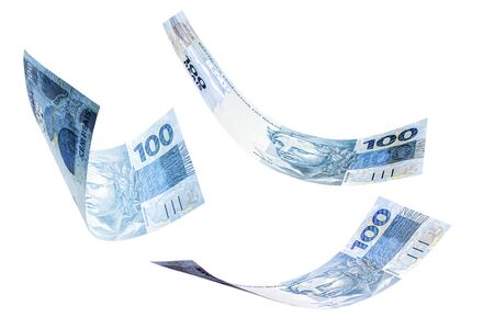 banknotes of one hundred reais from brazil falling on isolated white background. Concept of falling money, devaluation of the real or financial crisis.