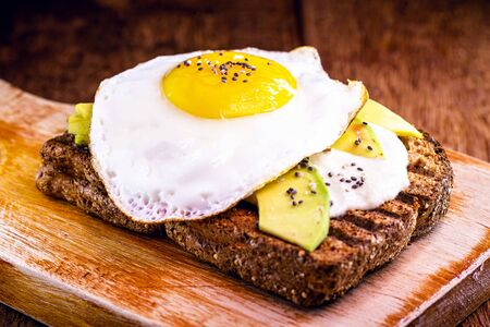 fried egg with avocado and brown bread toast.