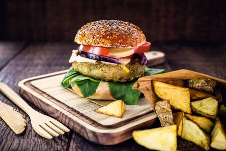 Vegetarian hamburger, sandwich made without meat, with recycled bamboo cutlery. Sandwich with arugula salad, red onion, tomato and mushroom. Portion of french fries with gourmet hamburger.