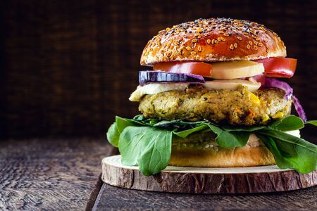 vegan burger on rustic wooden table, with vegetable burger and meat flavor. Healthy vegan food.
