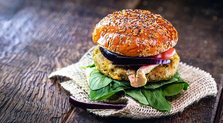 vegan food, meatless sandwich or elements of animal origin. Bread without eggs or milk, with vegetable and fiber or soy burger, on a rustic table. Vegan lifestyle.