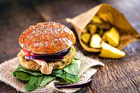 vegetarian burger with french fries in the background, gourmet food on rustic wooden table.