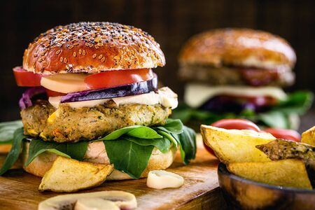 tasty vegan hamburger, hamburger made of vegetables and proteins, with arugula, purple tomato, mushroom and french fries. Healthy food without the addition of animal origin elements. Stockfoto