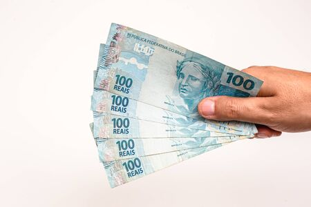 100 reais bills from Brazil, held by male hand on isolated white background. Banknotes of one hundred reais from brazil, payday.