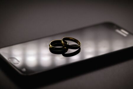 golden wedding rings on a mobile phone. Concept of infidelity or virtual betrayal through the smartphone.
