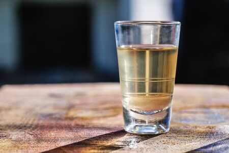 Several glasses of brazilian cachaça isolated on rustic wooden background, variations and types of brazil cachaça, typical drink from brazil.
