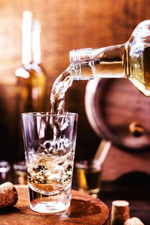 glass of cachaça, in a rustic setting. Cachaça or pinga, Brazilian drink from sugar cane. Rustic bar setting, Brazilian still.