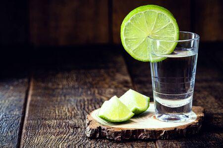 high quality distilled alcohol. Brazilian cachaça (called pinga) taken with lemon, drip, vodka, white rum, spirits, ozo, sake or brandy. Drink on rustic wooden background.