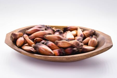 Typical araucaria tree seed used as a condiment in Brazilian cuisine in winter. Brazilian pine in brown wooden rustic bowl.