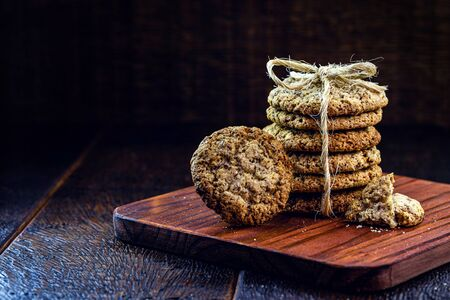 Whole grain cookies with cereals, dried fruits and chocolate on old wooden table