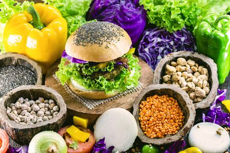 roasted vegan hamburger, made of vegetables and proteins. Healthy and vegetarian life concept. Colorful food, peppers, red cabbage, tomatoes, onions, chickpeas, soy, lettuce and lye Reklamní fotografie