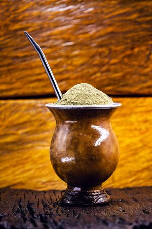 Gaucho yerba mate tea, the chimarão, typical brazilian drink, traditionally in a cuiade bombilla stick gourd against wooden background. Rio Grande do Sul, preferred drink of the gauchos. Stock Photo