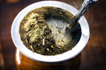 Yerba mate tea in calabash on wooden table. Traditional Argentine, Uruguayan and Brazilian drink. typical drink from grande do sul Standard-Bild