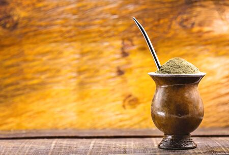 Yerba mate tea in wooden bowl on wooden table. Traditional drink from Brazil, Argentina, Paraguay and South America. Standard-Bild