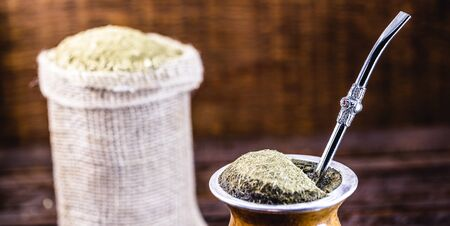 Gaucho yerba mate tea, the chimarrão, a typical Brazilian drink, traditionally in a bombilla stick cuiade gourd against a wooden background. Rio Grande do Sul, favorite drink of the gauchos.
