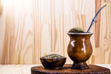 Traditional Argentinian, Brazilian and Uruguayan yerba tea in a gourd gourd with bombilla stick against wooden background