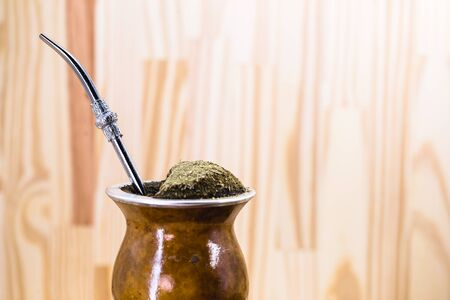 Traditional Argentinian, Brazilian and Uruguayan yerba tea in a gourd gourd with bombilla stick against wooden background Standard-Bild