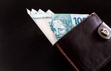 One hundred reais from Brazil banknotes in black leather wallet isolated on black background
