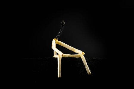 Concept of weakness or sadness, lonely. Image of a man made of matchstick. Small and depressive in the dark, erased and losing the flame. Stock Photo