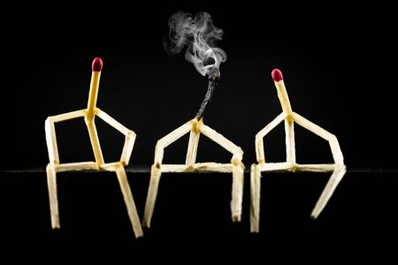 Concept of loneliness or depression. Image of three men with matchsticks sitting in the dark, one of them sad and erased.