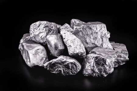 piece of silver or platinum on the stone floor, on black background. Export ore from south africa