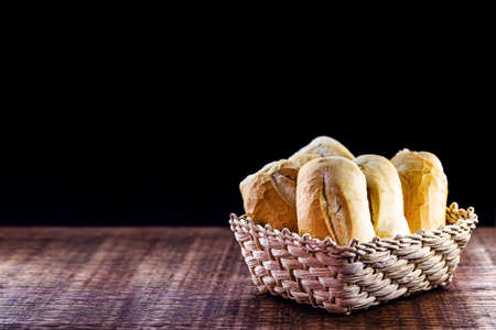various traditional breads from brazil, on rustic wooden background in isolated straw basket. Space for text on black background. National day of Brazilian French bread. Banque d'images