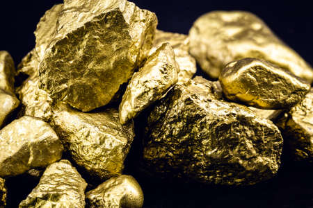 nugget of raw gold, the most expensive gemstone in the world. Mining and mineral extraction concept.