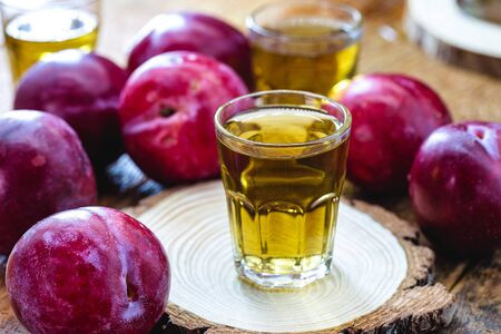 glass of plum liqueur, drink made from fruit-based alcohol. Rustic wood background.