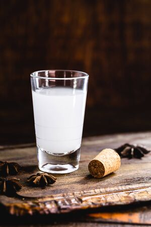 Ouzo or Uzo, is a Greek anise brandy, traditional strong alcoholic drink in glasses on the old wooden table. Greek tradition, drink of the gods. Place for text