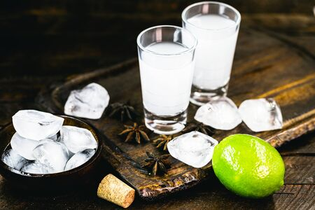 Ouzo or Uzo, is a Greek anise brandy, traditional strong alcoholic drink in glasses on the old wooden table. Greek tradition, drink of the gods. Place for text Standard-Bild