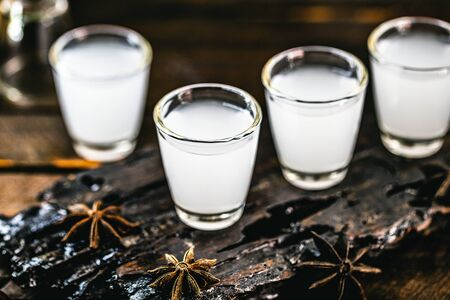 Traditional Greek vodka, known as Uzo or ouzo in shot glasses on a rustic wooden background. Space for text. Standard-Bild