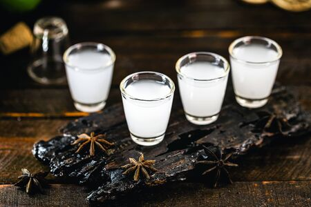 Traditional arabic alcohol drinks Raki with anise, rustic wooden background with space for text.