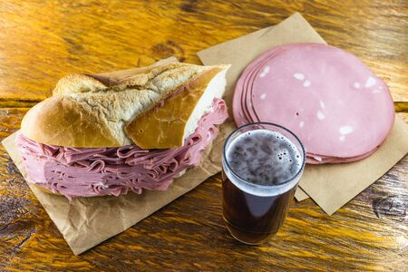 Bread snack with mortadella on a rustic empress table, with typical Brazilian beer.