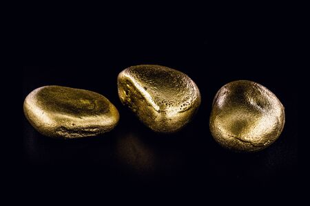 Gold nugget, large gold stone closeup isolated on black background. Concept of finance, luxury or wealth. Stock Photo