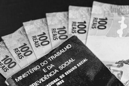 Brazilian work card with 100 reais bills, document written in Portuguese Ministry of Labor and Social Security. Concept of emergency aid paid in the quarantine period. 写真素材