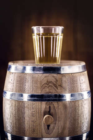 aged oak barrel with glass of distilled beverage used for fermented drinks such as rum, cachaça, vodka, among others. Spot focus on the barrel. Archivio Fotografico
