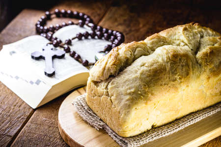 homemade bread made in the Easter and Eucharist period, called Christ bread, religious symbol, with Bible and crucifix in the background