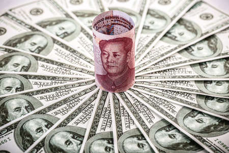 Chinese money, Renminbi, 100 yuan note, cornered by many hundred dollar bills. Financial dispute concept between china and united states