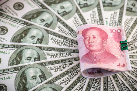 American money banknotes around a Chinese money bill, concept of yuan versus dollar Stock Photo