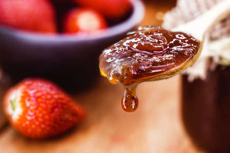 wooden spoon with handmade strawberry jam dripping a drop, copy space